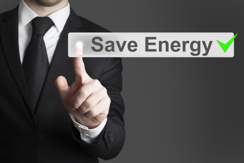 businessman in black suit pushing flat touchscreen button save energy eco mode